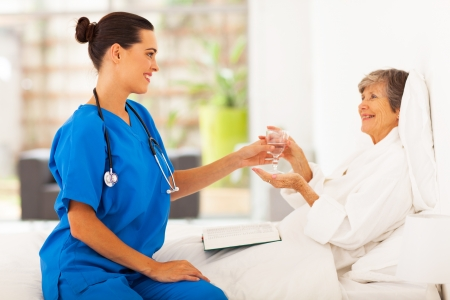 bring: caring young caregiver bring a glass of water to senior woman on bed