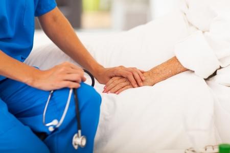 doctor en medicina de la mano paciente mayor y consolándola Foto de archivo