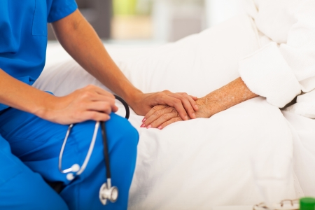 elderly care: medical doctor holding senior patients hands and comforting her