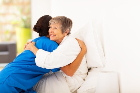 grateful: happy elderly woman hugging caregiver on bed Stock Photo