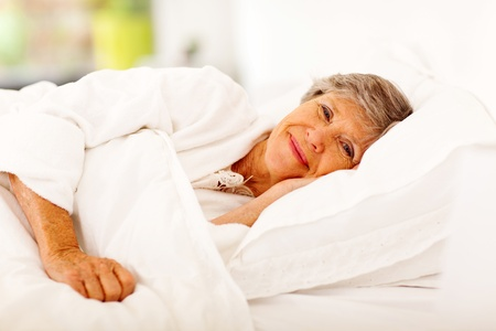 happy senior woman sleeping on bed photo