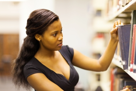 female african american college student looking for book in library Stock Photo - 17718226