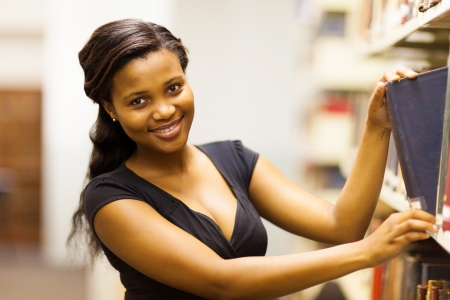 happy african american college girl looking for book in library Stock Photo - 17718215