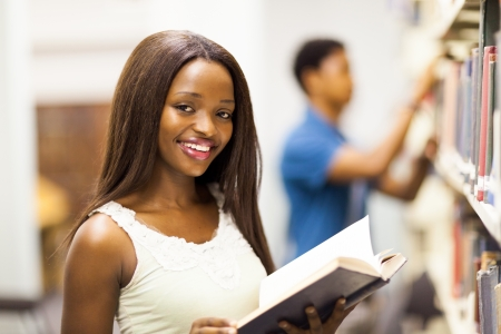 female african american university student reading book in library photo