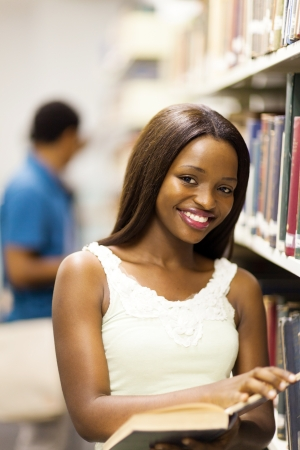 cute african american college girl reading in library photo