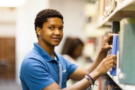 young male african uni student looking for books in library Stock Photo - 17718221