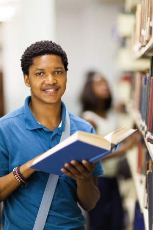 happy african american college boy reading in library Stock Photo - 17718229
