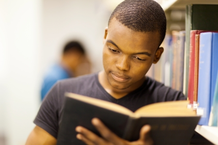 student reading: male african university student reading in library
