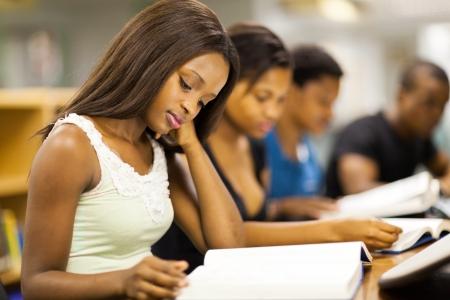 hombre estudiando: grupo africano de los estudiantes universitarios estadounidenses que estudian juntos