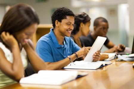 afroamericanas: feliz masculino estudiante africano americano universitario que usa el ordenador tableta