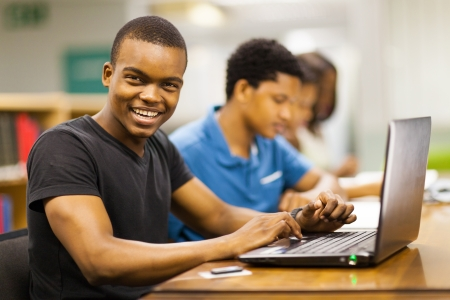 happy male african college student using laptop in library photo