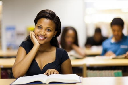 pretty african college student reading book in library Stock Photo - 17718202