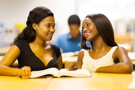 two african college girls reading book in library photo