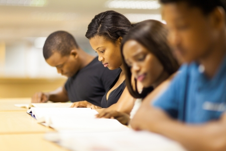 students studying: group of african college students reading in library