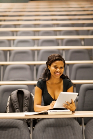 female african american college student in lecture hall with tablet computer photo