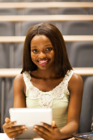female african college student using tablet computer in lecture room photo