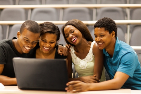 group of african american college students using laptop in lecture room photo