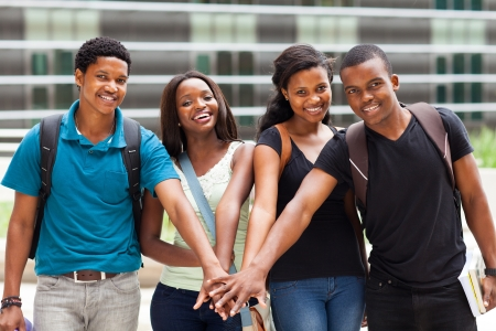 group of african college students putting hands together photo