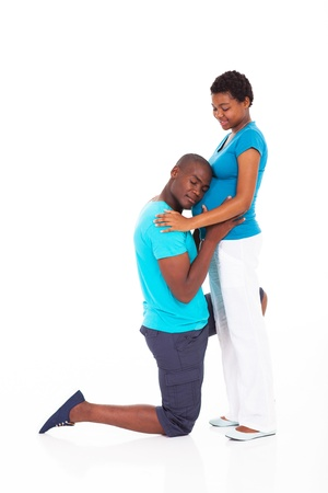 hugging knees: loving african american husband knee down and listen pregnant wifes belly Stock Photo