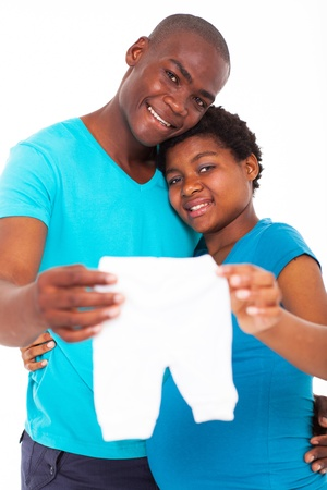 expecting african american couple holding baby clothes photo