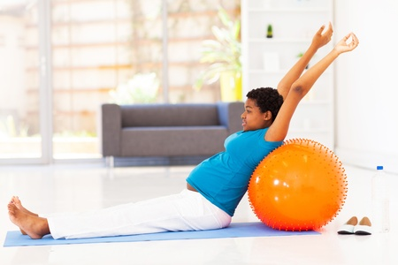 pregnant african american woman exercising on floor at home photo