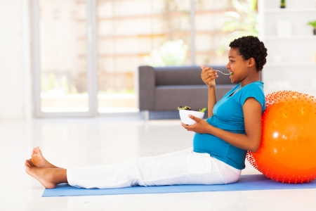 pregnant african american woman eating healthy salad on exercise mat photo