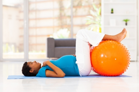 pregnant african woman workout on exercise mat at home photo