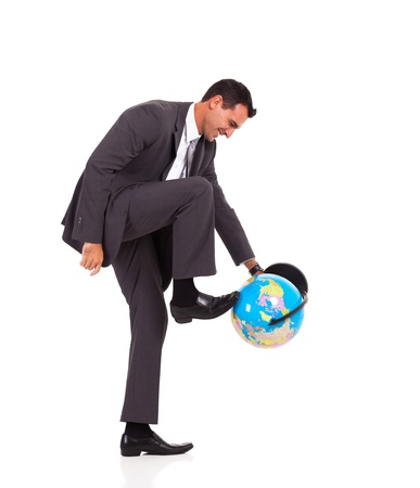 young businessman turning globe with his foot isolated on white photo