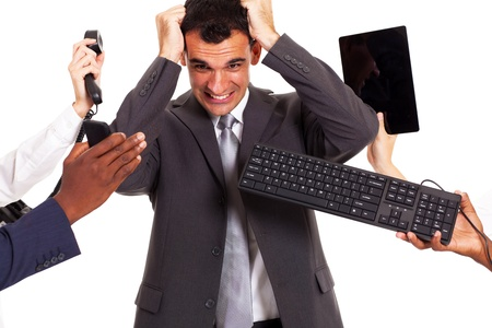 frustrated businessman around by multiple office tools photo