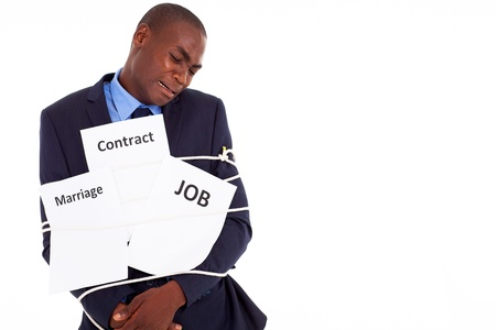 unhappy worker: african american businessman in deep trouble being tied with contract job and marriage