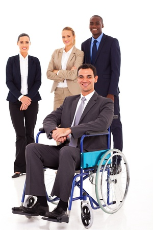 well dressed girl: businessman in wheelchair with colleagues in background Stock Photo