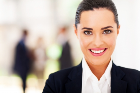 navy blue suit: attractive young businesswoman face closeup in office
