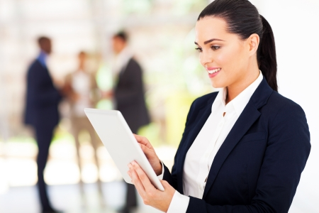 navy blue suit: modern businesswoman using tablet computer in office Stock Photo