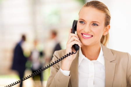 happy female office worker talking on landline phone photo