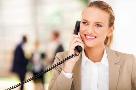 phone handset: happy female office worker talking on landline phone Stock Photo