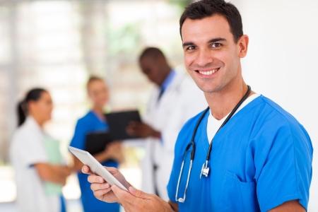 enfermera: cirujano apuesto m�dico con equipo Tablet PC en el hospital