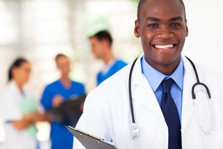 doctor: handsome african american medical doctor with colleagues in background