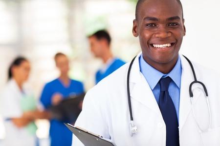 lekarz: przystojny afroamerykanin lekarz z kolegami w tle Zdjęcie Seryjne