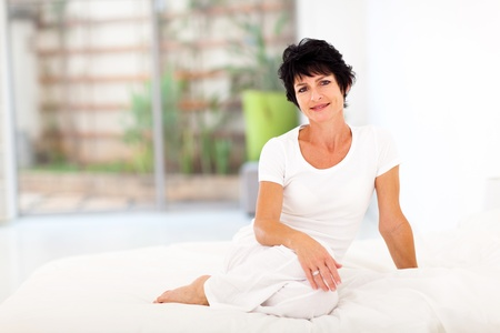 woman middle age: beautiful middle aged woman sitting on bed Stock Photo
