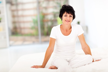 good looking woman: happy middle aged woman sitting on bed at home Stock Photo