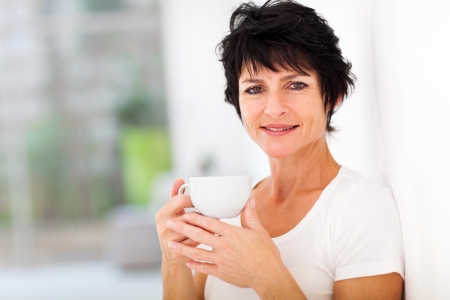 european people: attractive mid age woman enjoying coffee at home