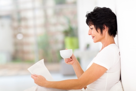 reading a newspaper: pretty mature woman reading newspaper on bed at home