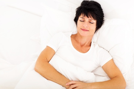 overhead view of elegant middle aged woman sleeping on bed photo