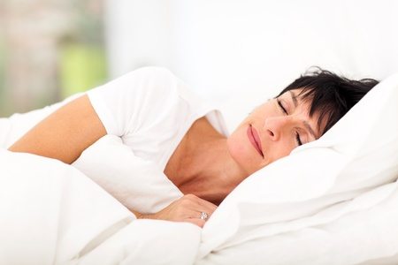 white pillow: cute mature woman sleeping on bed