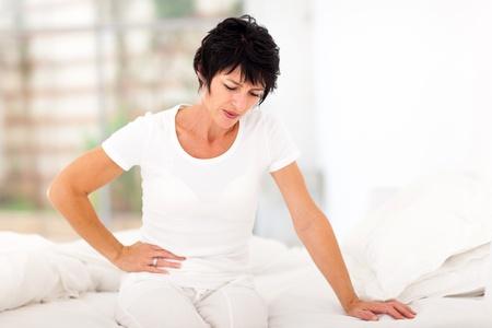 желудок: Зрелая женщина сидит на кровати и имеющих боли в животе