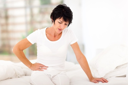 mature woman sitting on bed and having stomach ache Standard-Bild