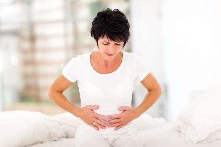 dolor de estomago: mediados de mujer de la edad que tiene dolor de estómago en el hogar Foto de archivo