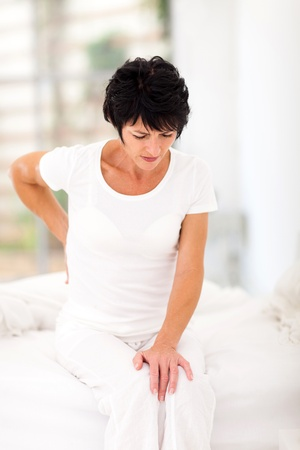 woman in pain: middle aged woman sitting on bed having back pain