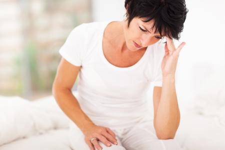 dolor de cabeza: mujer de mediana edad sentada en la cama y con dolor de cabeza Foto de archivo