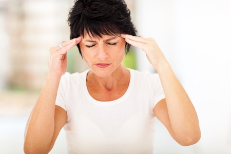 mid age woman having headache and massaging forehead photo